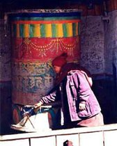 Tibetan Buddhist Nun in Himalayas of Nepal turning a large prayer